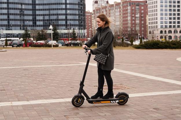 Piękna dziewczyna w płaszczu jeździ skuterem elektrycznym po mieście