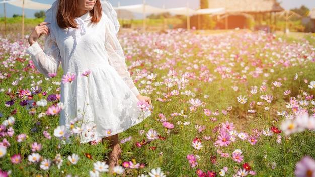 Piękna dziewczyna w polu kosmosu na niebieskim tle nieba, piękny lanscepe w azji.