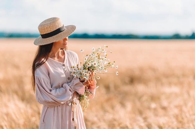 Piękna dziewczyna w polu pszenicy z dojrzałej pszenicy w ręce