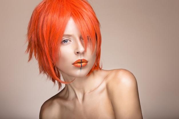 Piękna dziewczyna w pomarańczowym stylu cosplay peruki z jasnymi kreatywnymi ustami.