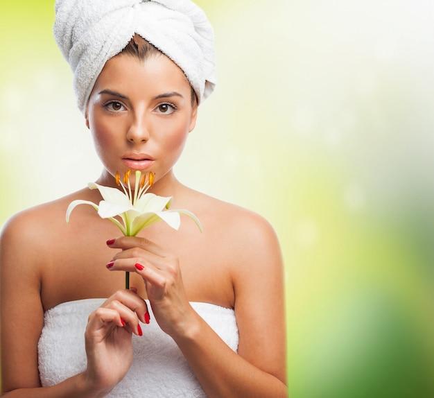 Piękna dziewczyna w ręcznik trzyma białą lilię