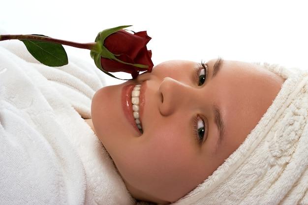 Piękna dziewczyna w ręcznik z różą relaks po prysznicu na białym tle