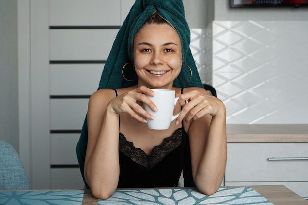 Piękna dziewczyna w ręczniku na włosach siedzi w kuchni przy filiżance kawy. kobieta patrząc na kamery i uśmiechnięty