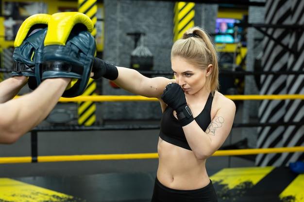 Piękna dziewczyna w rękawicach bokserskich uderza w łapy trzymane przez jej trenera.