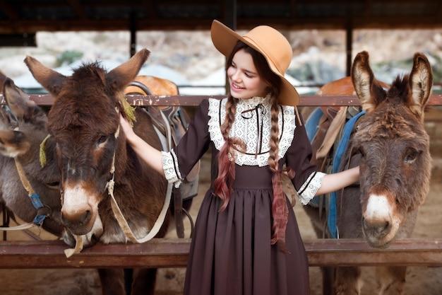 Piękna dziewczyna w retro sukni i kapeluszu na osła gospodarstwie rolnym karmi osła. żniwa. jesienny czas.