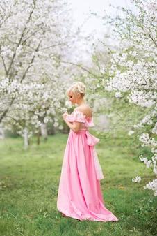 Piękna dziewczyna w różowej sukience na wiosnę idzie do kwitnącego ogrodu.