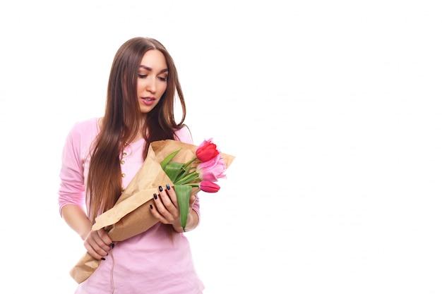 Piękna dziewczyna w różowej sukni z kwiatów tulipanami w rękach na białym tle. pojedynczo na białym.