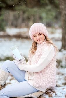 Piękna dziewczyna w różowych ubraniach z termosem pije herbatę i uśmiecha się do zimowego lasu
