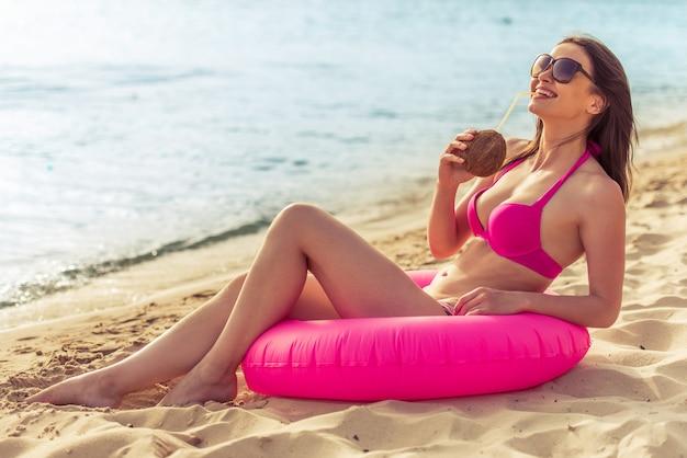 Piękna dziewczyna w różowym stroju kąpielowym pije mleko kokosowe.