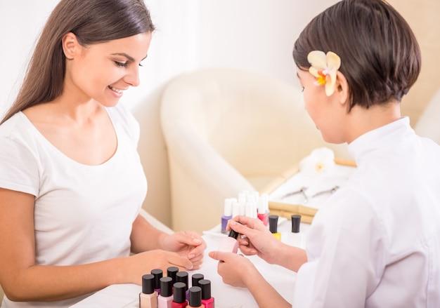 Piękna dziewczyna w salonie piękności robi paznokcie.