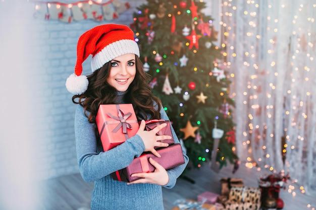 Piękna dziewczyna w santa hat z prezentem na choinkę.