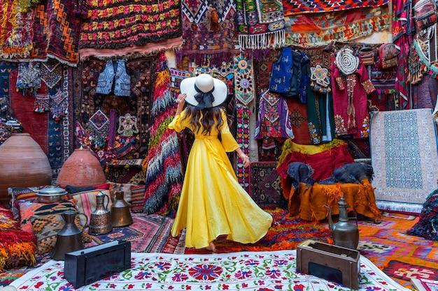 Piękna dziewczyna w sklepie z tradycyjnymi dywanami w mieście goreme, kapadocja w turcji.
