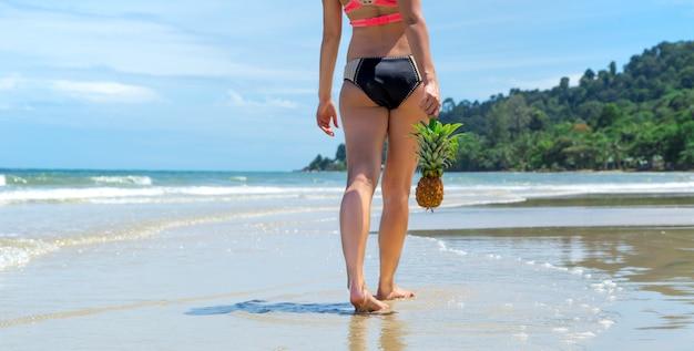Piękna dziewczyna w słomkowym kapeluszu i chodzącym ananasie na egzotycznej plaży, dobre jedzenie i odpoczynek