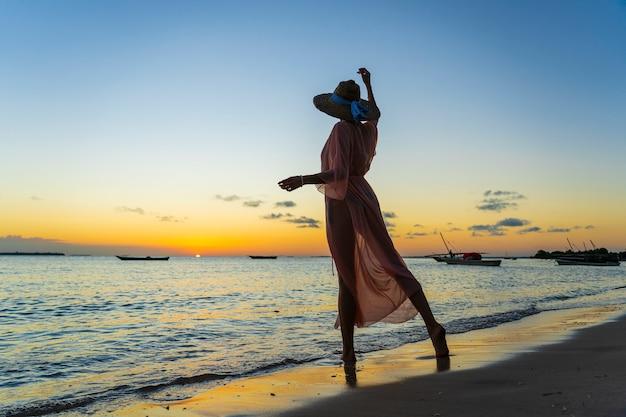 Piękna dziewczyna w słomkowym kapeluszu i pareo na plaży podczas zachodu słońca na wyspie zanzibar, tanzania, afryka wschodnia. koncepcja podróży i wakacji