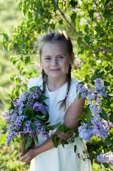 Piękna dziewczyna w słomkowym kapeluszu w liliowym ogrodzie. dziewczyna z kwiatami bzu na wiosnę. prace ogrodowe.