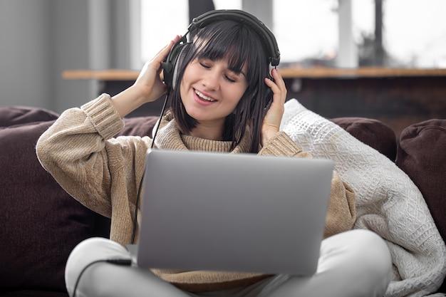 Piękna dziewczyna w słuchawkach lubi słuchać muzyki w domu na kanapie z laptopem.