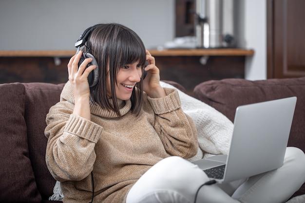 Piękna dziewczyna w słuchawkach, słuchanie muzyki w domu na kanapie z laptopem.