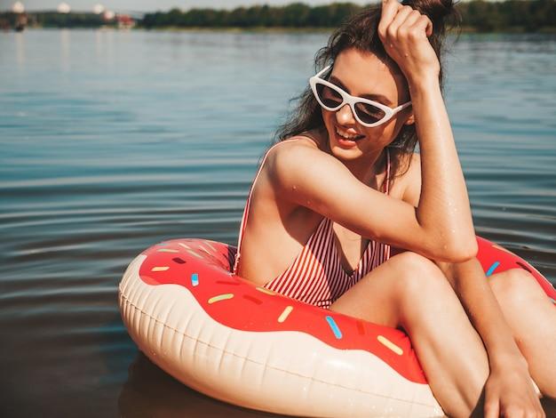 Piękna dziewczyna w strojach kąpielowych pływających z nadmuchiwanym pączkiem na morzu