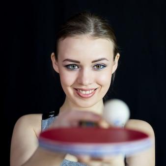 Piękna dziewczyna w stroju sportowym rzuca piłkę na rakietę tenisową.