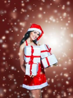 Piękna dziewczyna w stroju świętego mikołaja z zakupami na tle bożego narodzenia