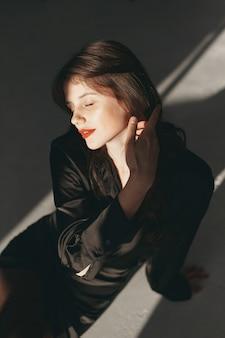 Piękna dziewczyna w studiu. stylowa kobieta w czarnej sukni.