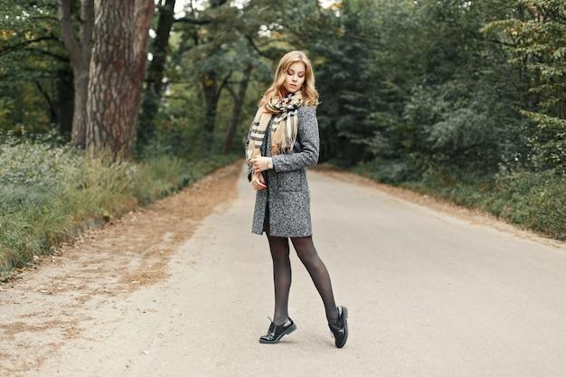Piękna dziewczyna w stylowe ubrania jesień pozowanie w parku.