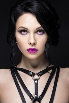 Piękna dziewczyna w stylu gotyckim ze skórzanymi dodatkami i jasnym makijażem.