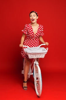 Piękna dziewczyna w stylu pin-up z rowerem