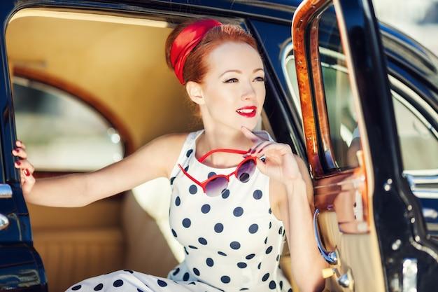 Piękna dziewczyna w stylu retro i rocznika samochodu