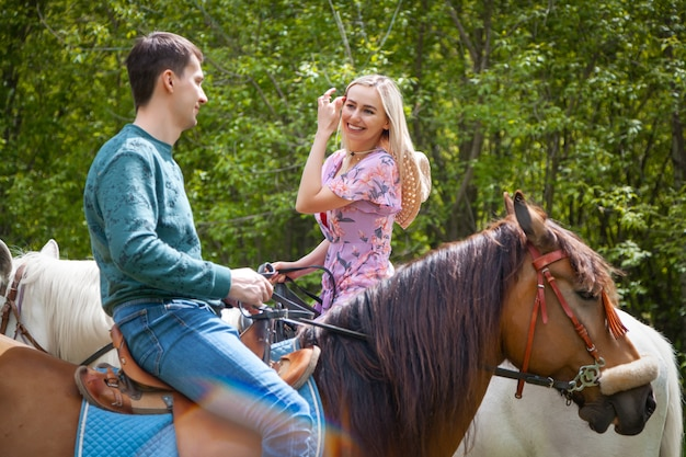Piękna dziewczyna w sukience kwiatowy link i młody człowiek chodzenie na koniach na przyrodę. styl życia miłośnicy randek na koniu