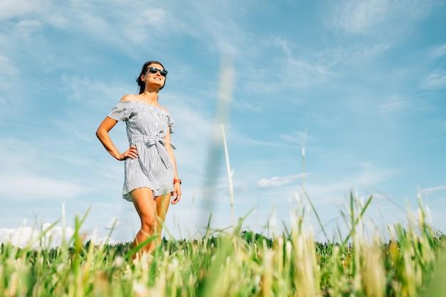 Piękna dziewczyna w sukience na zielonym polu. koncepcja ludzi i przyrody