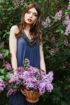 Piękna dziewczyna w sukience pozowanie w pobliżu krzaka bzów w letni dzień, fioletowe kwiaty w parku. wiosenny portret dziewczyny w przyrodzie w słońcu