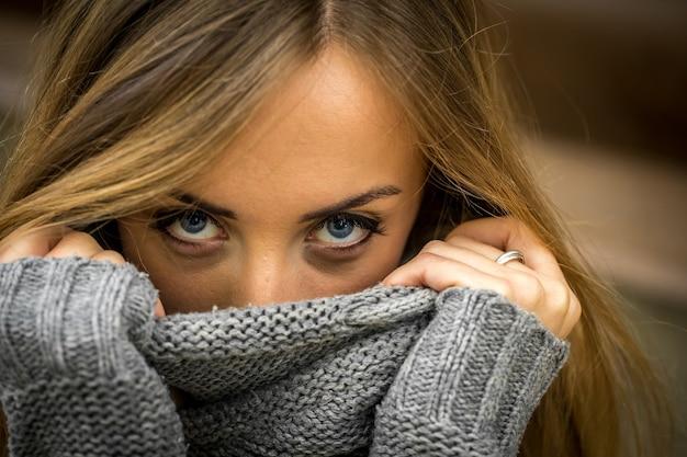 Piękna dziewczyna w sweter z długimi włosami i czerwonymi ustami na ścianie z drewnianych bali