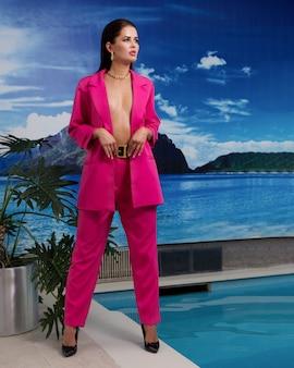 Piękna dziewczyna w szkarłatnym garniturze w basenie