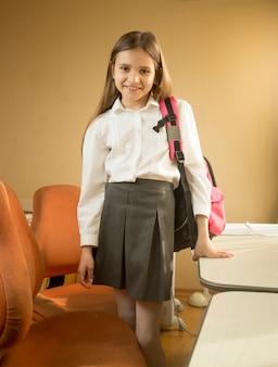Piękna dziewczyna w szkolnym mundurku pozuje z torbą w sypialni