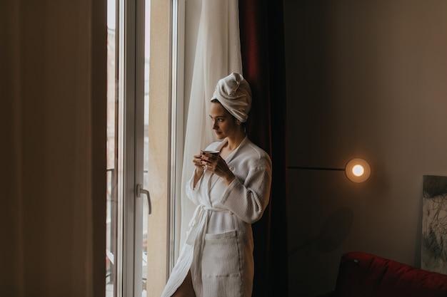 Piękna dziewczyna w szlafroku i ręczniku na głowie wygląda w zamyśleniu przez okno z filiżanką herbaty w dłoniach.