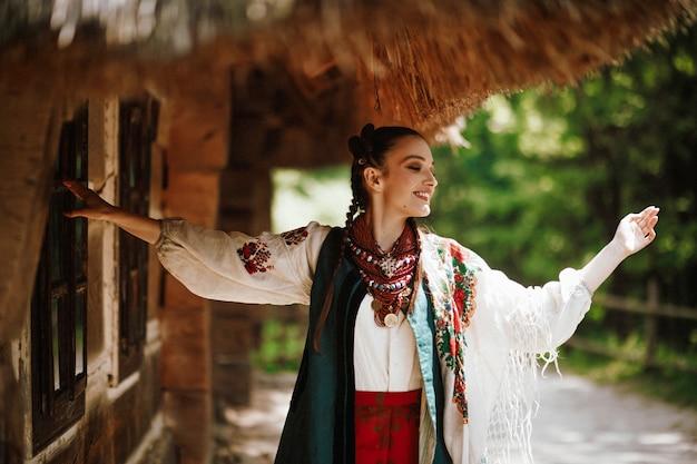Piękna dziewczyna w tradycyjnym ukraińskim stroju tańczy i uśmiecha się