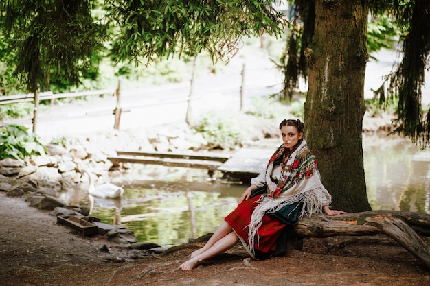 Piękna dziewczyna w ukraińskiej haftowanej sukni siedzi na ławce w pobliżu jeziora