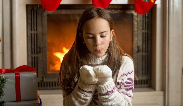 Piękna dziewczyna w wełnianym swetrze i rękawiczkach siedząca przy płonącym kominku