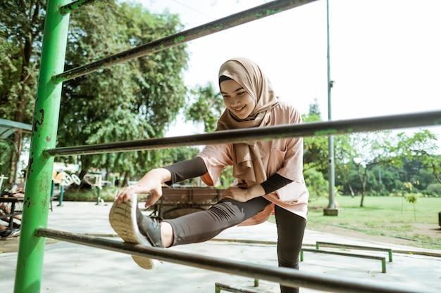 Piękna dziewczyna w welonie rozciąga nogę na żelaznym pręcie, zanim zacznie ćwiczyć, aby schudnąć