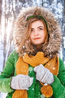 Piękna dziewczyna w zimowej kurtce i rękawiczkach na tle lasu