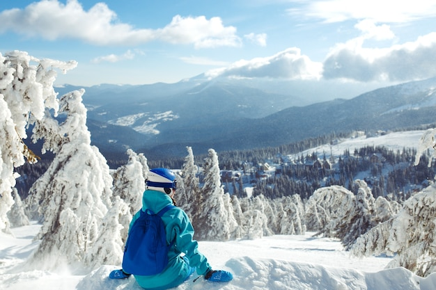 Piękna dziewczyna w zimowych ubraniach, niebieskim kasku i zielonej kurtce bawi się w górach.