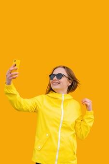Piękna dziewczyna w żółtej kurtce robi selfie na pomarańczowym tle