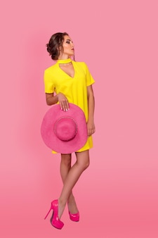 Piękna dziewczyna w żółtej sukience w okularach przeciwsłonecznych pozuje uśmiechając się na różowym tle w studio