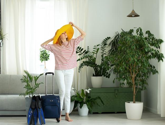 Piękna dziewczyna w żółtym kapeluszu zostaje w domu i planuje wyjazd na wakacje. walizka i płetwy do nurkowania. czekam na podróż.