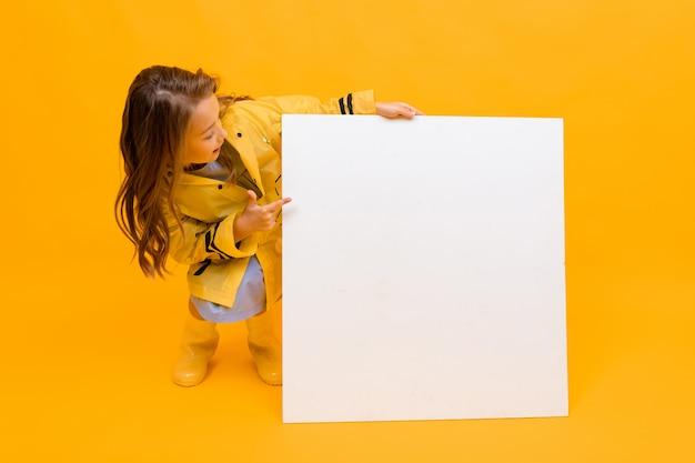 Piękna dziewczyna w żółtym płaszczu przeciwdeszczowym i gumowych butach siedzi obok pustego kwadratowego sztandaru w białym kolorze