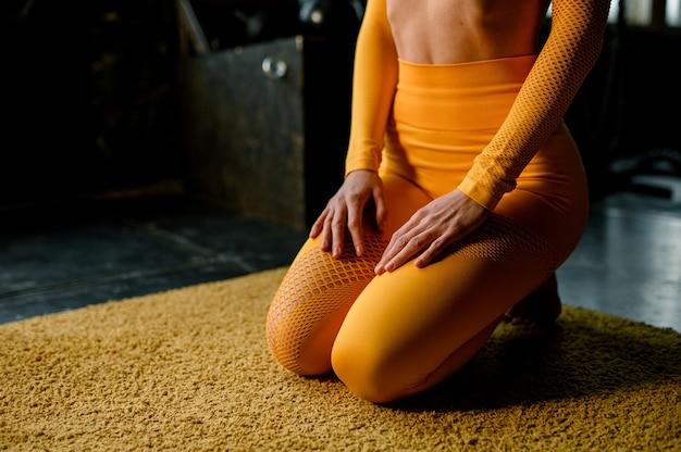 Piękna dziewczyna w żółtym stroju sportowym robi w jodze prawidłowo oddychając nowoczesną halą sportową