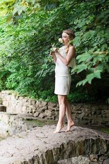 Piękna dziewczyna wącha białą różę