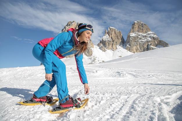 Piękna dziewczyna wędrówki w rakietach śnieżnych w dolomitach