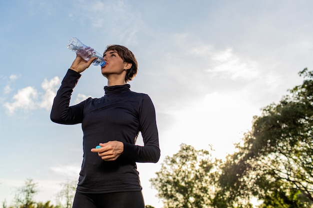Piękna dziewczyna wody pitnej z butelki w parku.